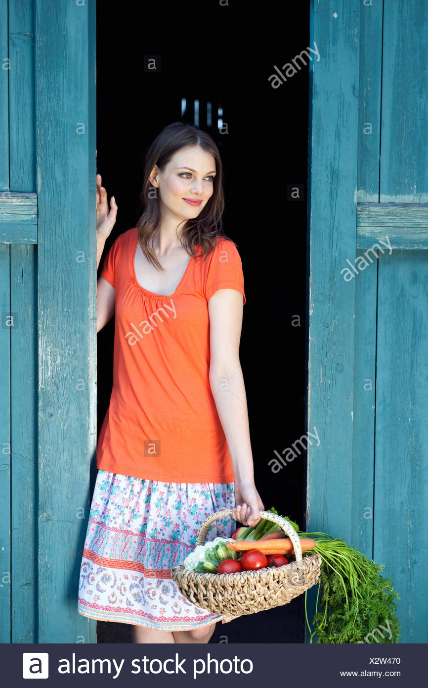 Germany, Bavaria, Woman holding home grown vegetables - Stock Image