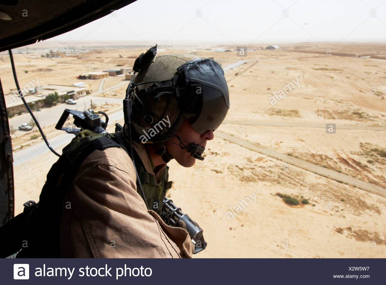 US Marine flight crew chief scans desert below Marine Corps UH-1N utility helicopter fitted weapons during combat operation Stock Photo