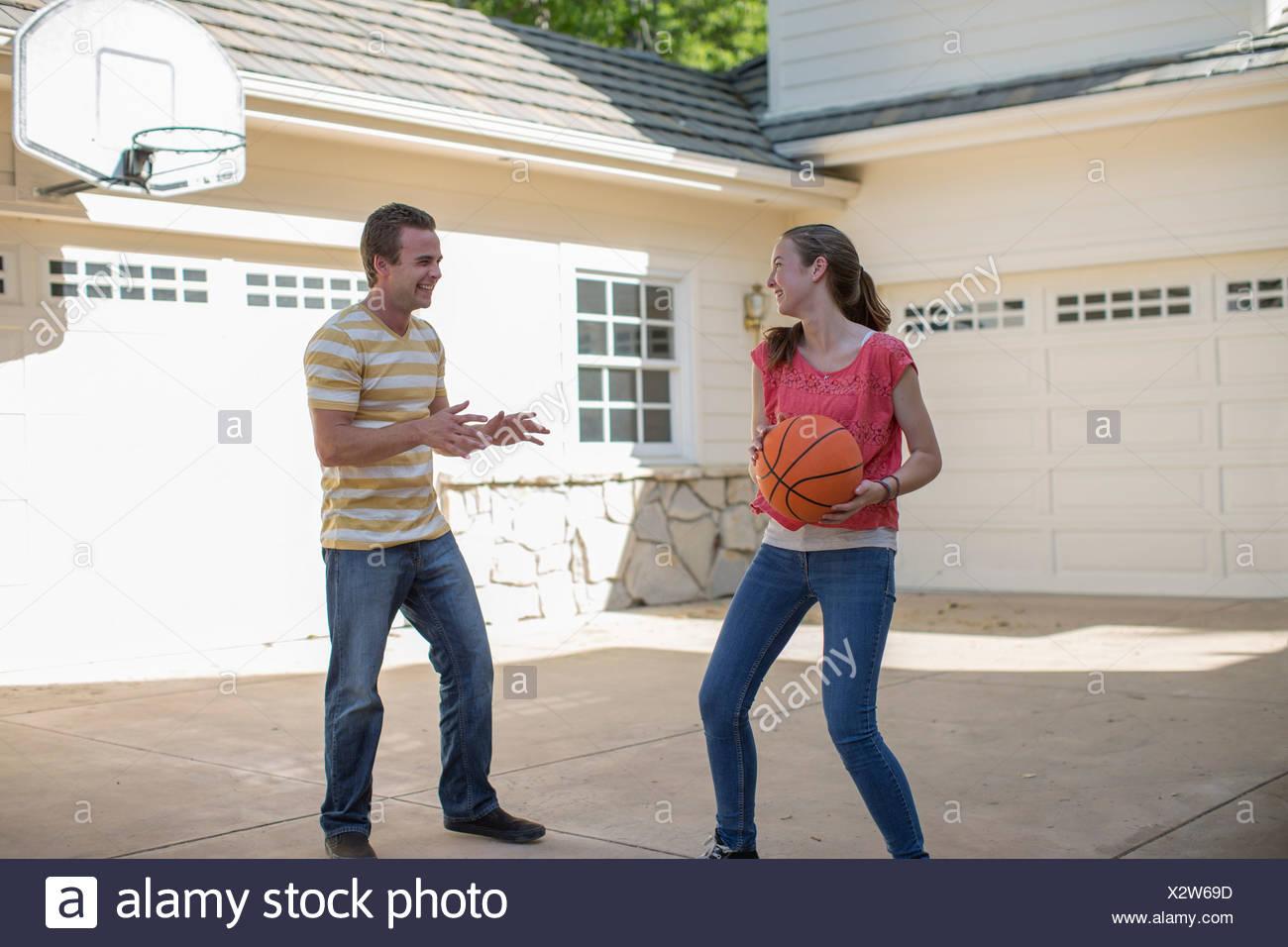 Brother and sister playing basketball - Stock Image