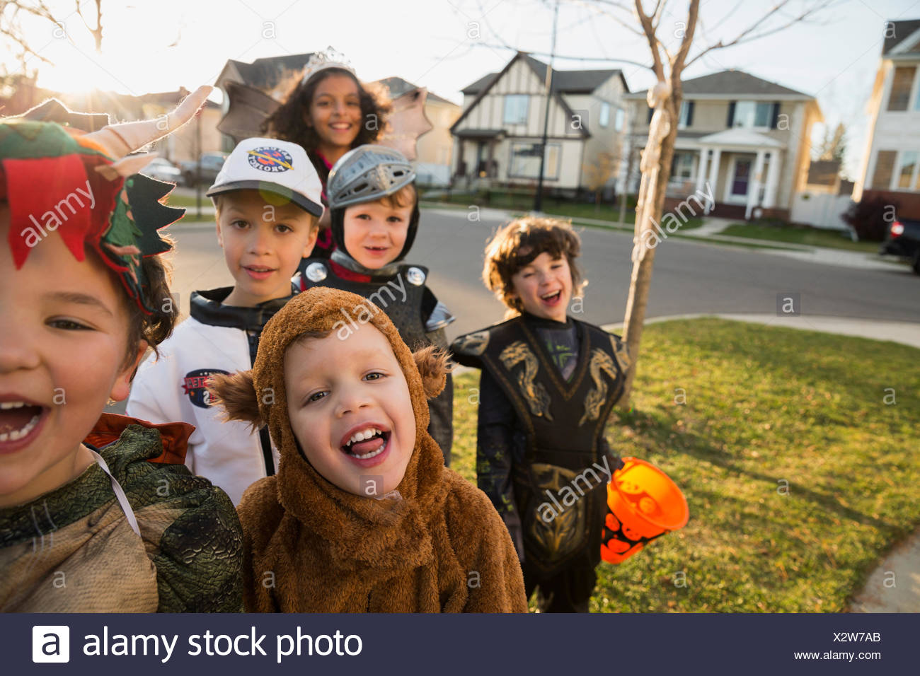 Portrait enthusiastic kids in Halloween costumes - Stock Image