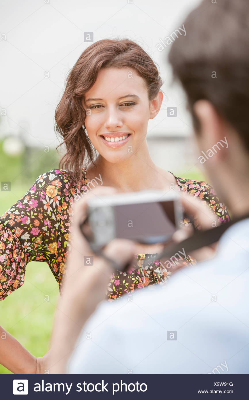 Happy young woman being photographed by man in park - Stock Image