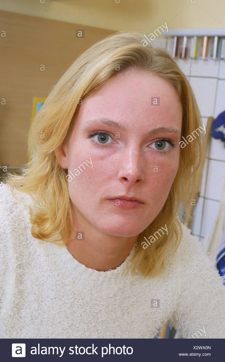 Young adult natural woman looking at camera, looking unhappy , facing camera , head and shoulders serious expression front view - Stock Image