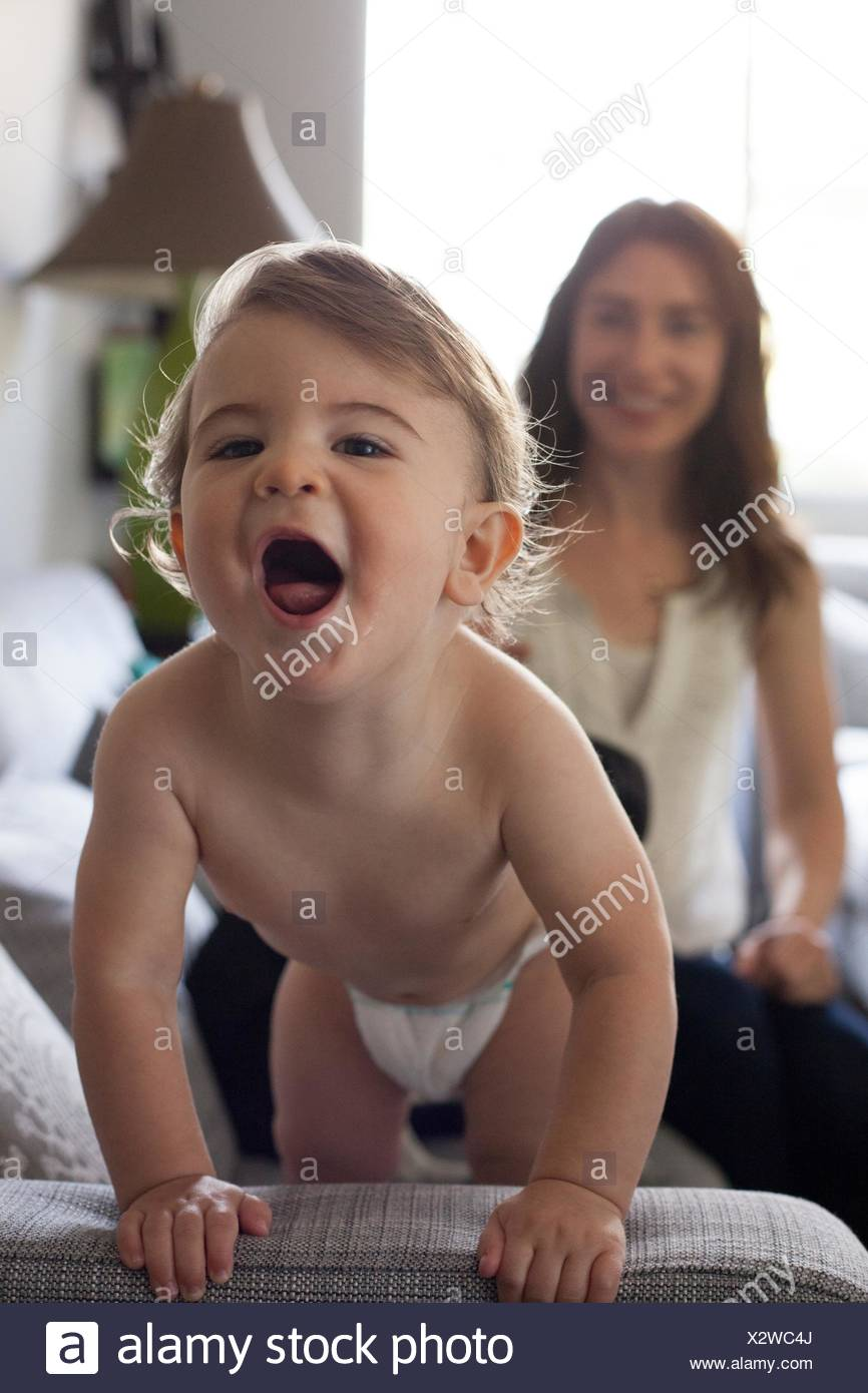 Baby boy holding onto sofa looking at camera open mouthed - Stock Image