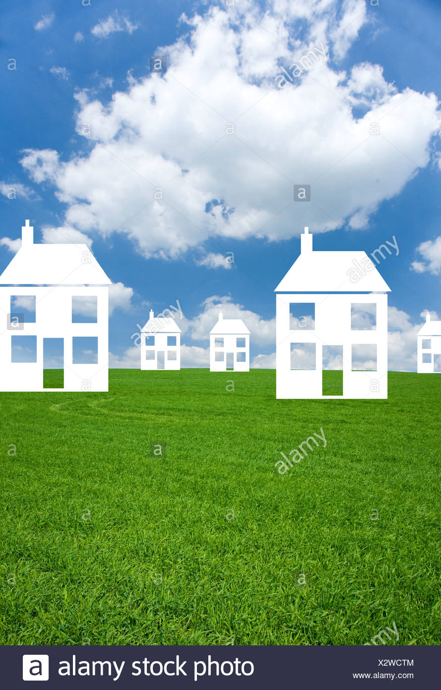 Cut out houses in grass field - Stock Image