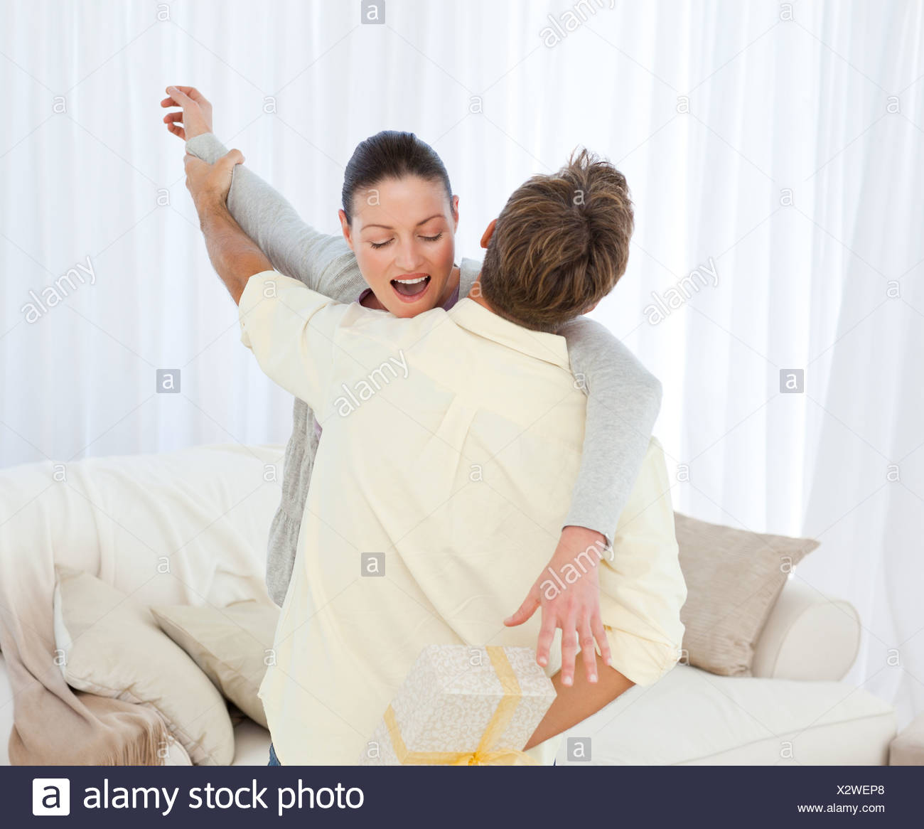 Excited woman catching a present hidden behind her boyfriend - Stock Image