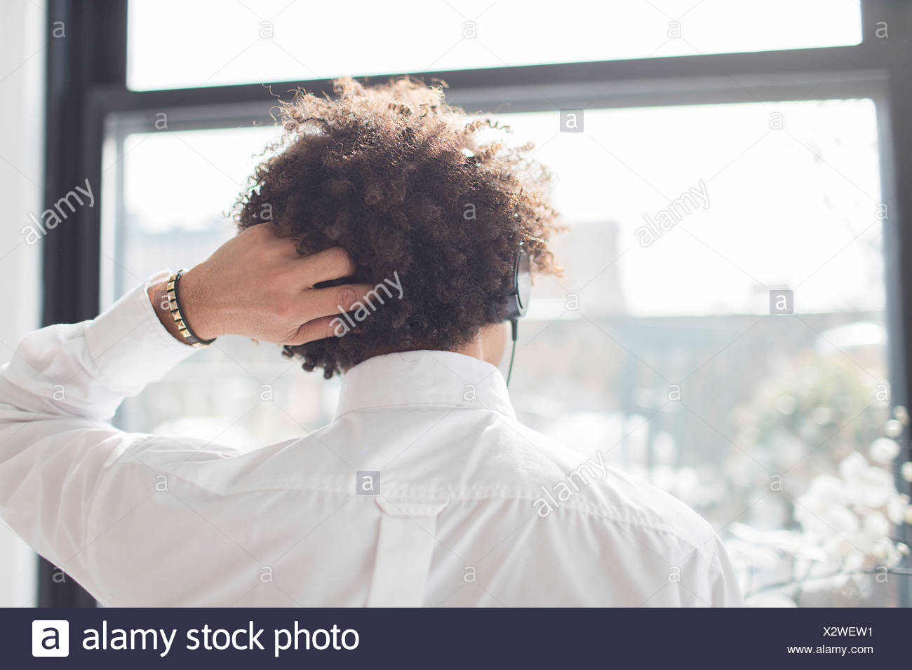 Young man scratching head, rear view Stock Photo