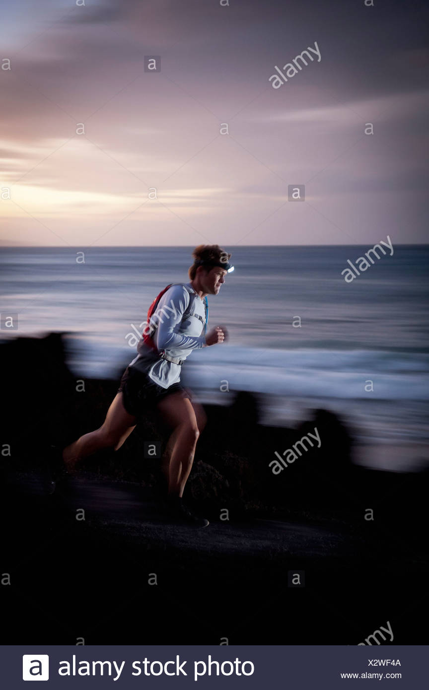 Blurred view of runner on rocky trail - Stock Image