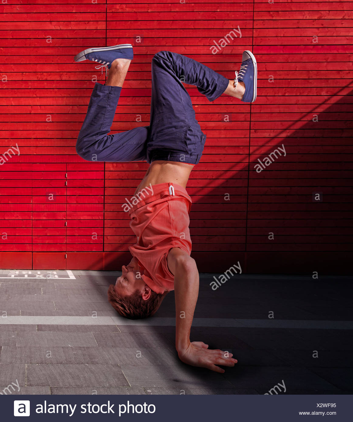 Break dancer doing handstand against red wall background - Stock Photo