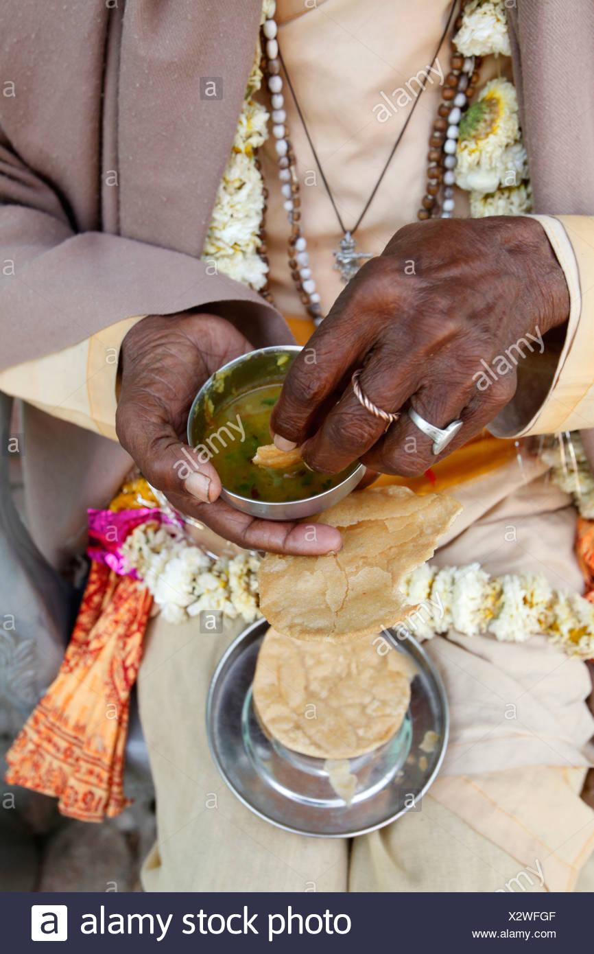 Sadhu eating vegetarian food Dauji. India. - Stock Image