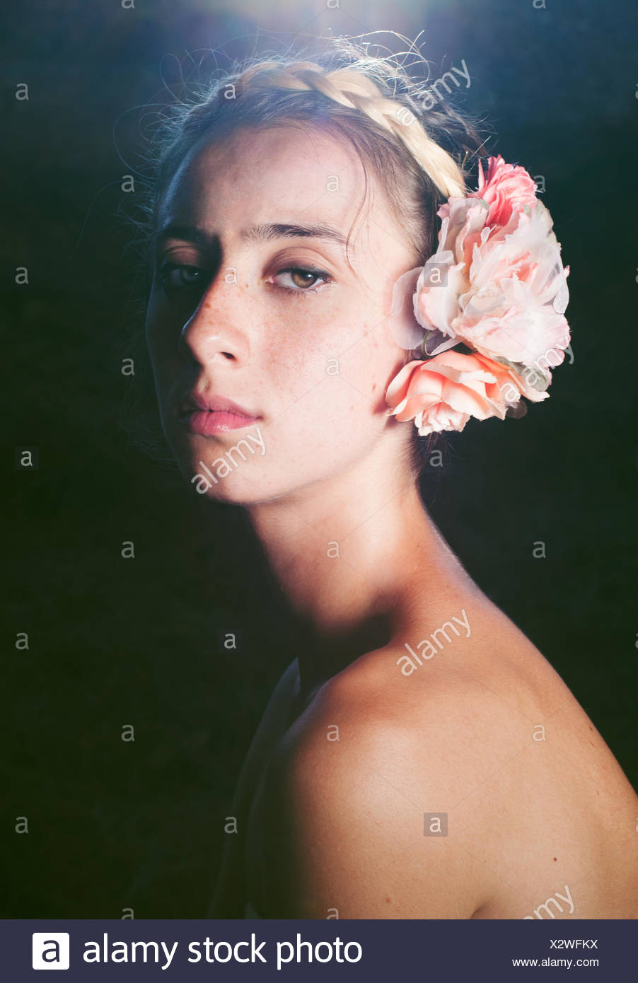 Portrait of woman with flower in hair - Stock Image