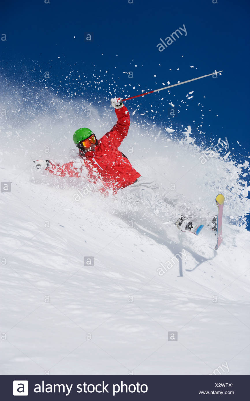 Man in red falling mid carve off-piste. - Stock Image