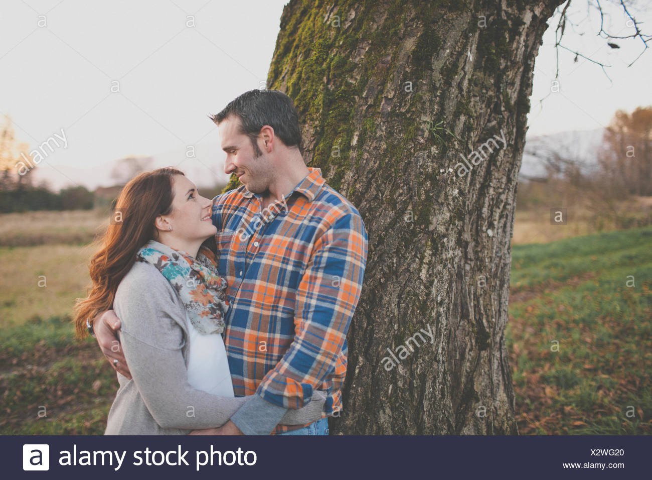 Portrait of a husband and wife smiling at each other. - Stock Image