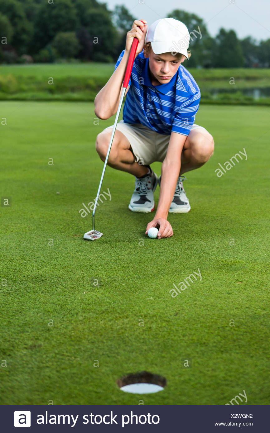 Teenage boy placing ball on tee on golf course - Stock Image
