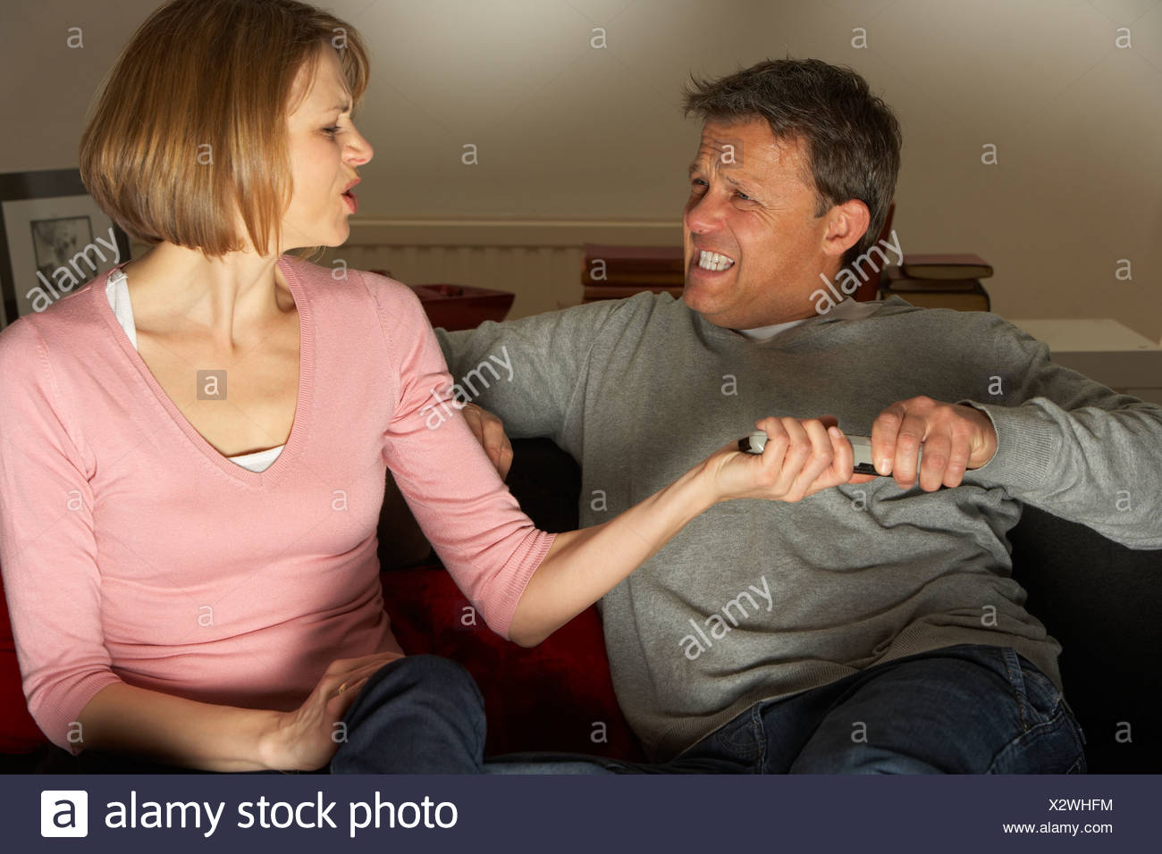 Couple Discussing Choice Of Television Channel - Stock Image