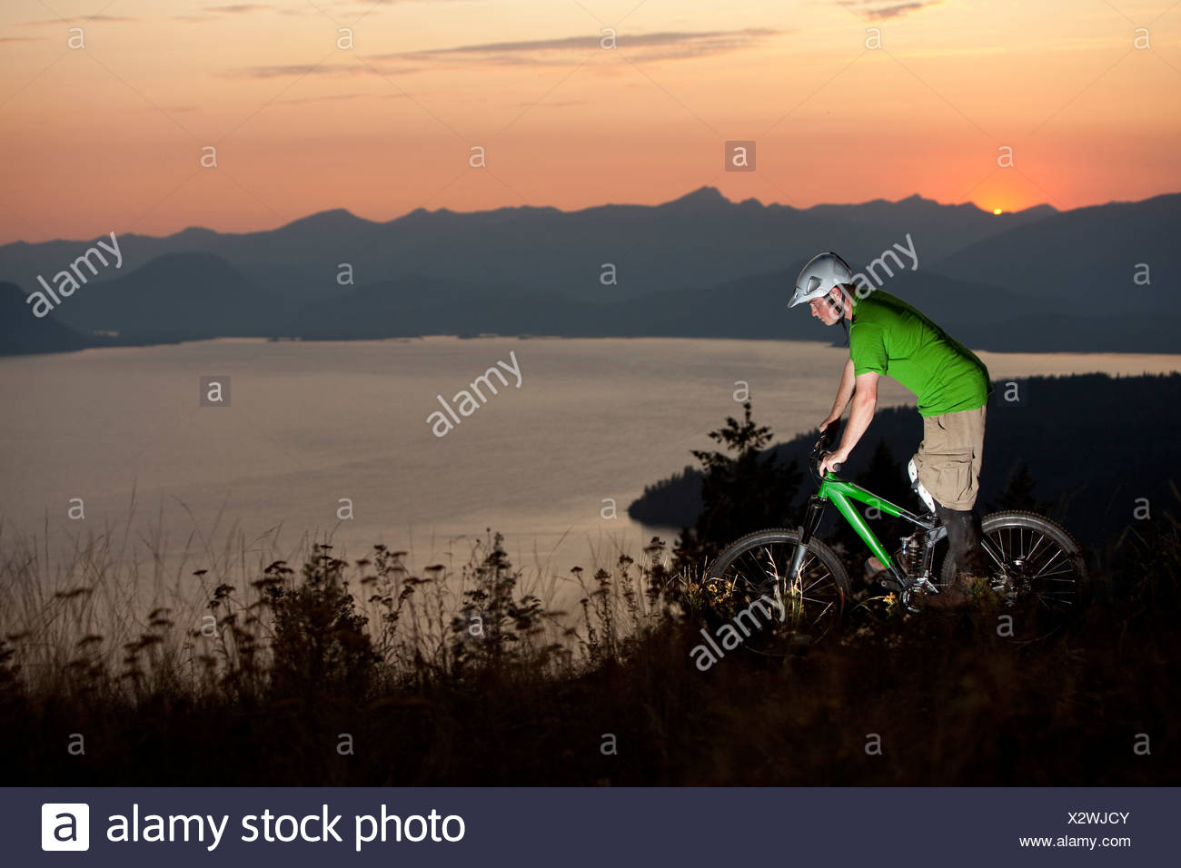 Young adult mountain biking at sunrise in Idaho. - Stock Image