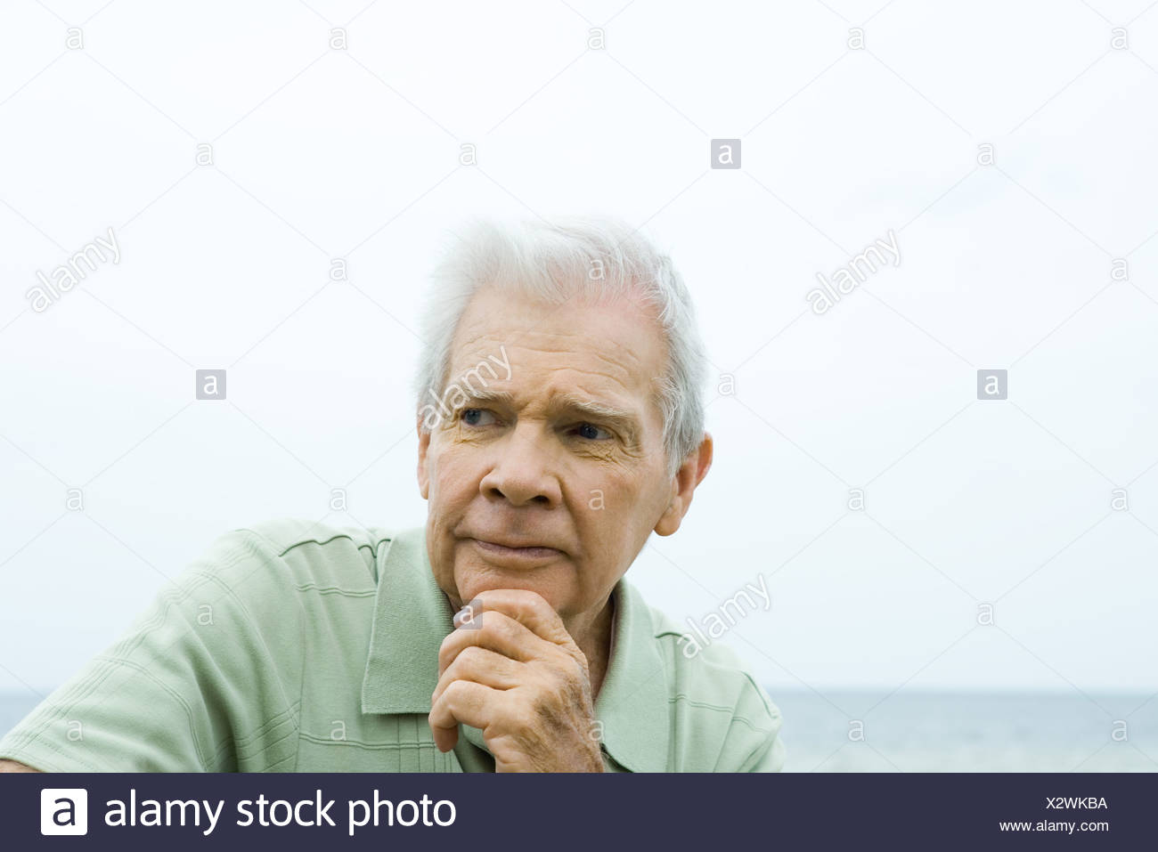 Senior man with hand under chin, furrowing brow, looking away - Stock Image