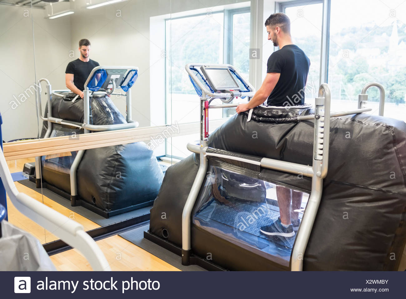 Injured athlete working out on treadmill - Stock Image