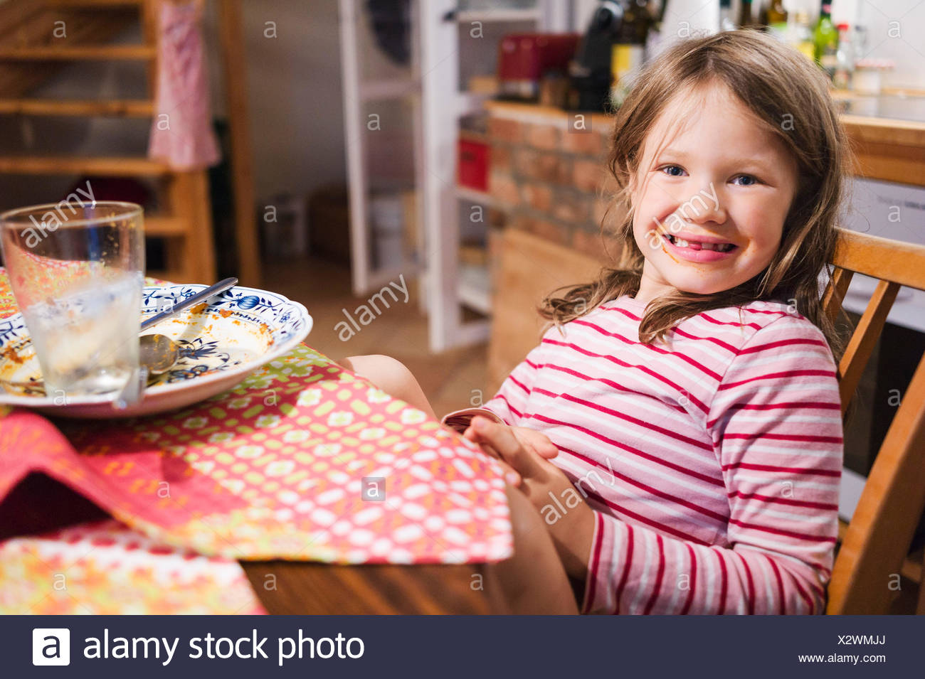 Girl sits at the table after food and grins with smeared mouth in the camera - Stock Image