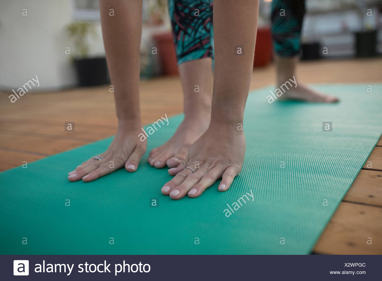 Close up woman practicing yoga on yoga mat with foot between hands - Stock Image