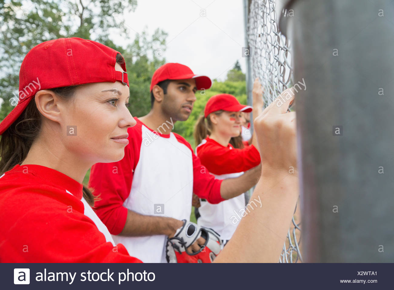 Baseball team watching game from behind fence - Stock Image