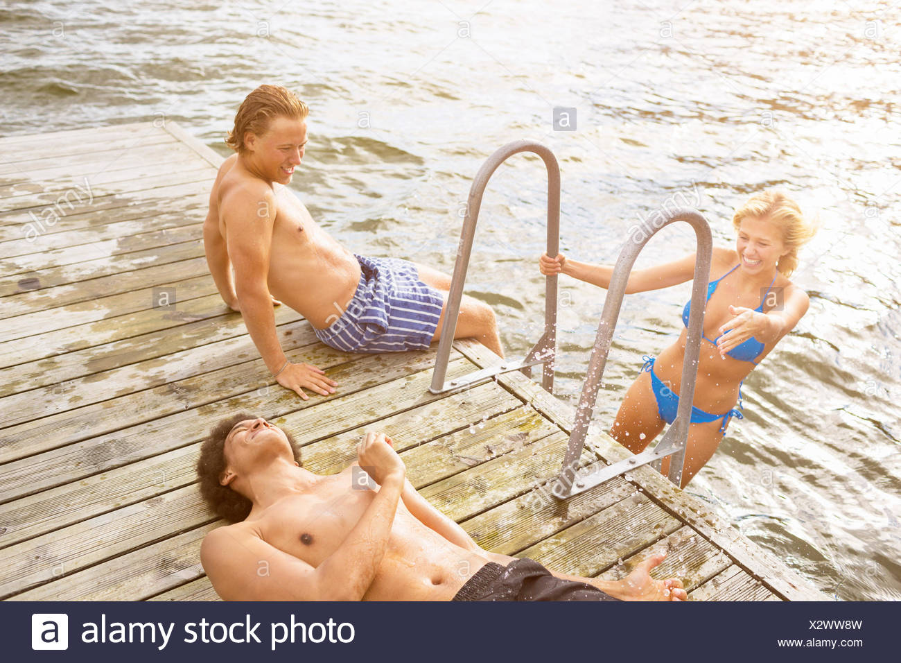 High angle view of friends enjoying vacation on boardwalk at lake - Stock Image