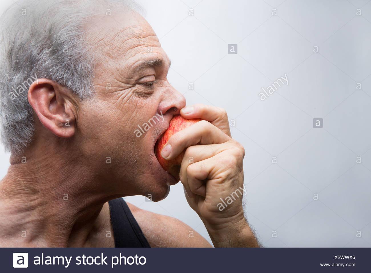 Senior man eating apple, close up - Stock Image