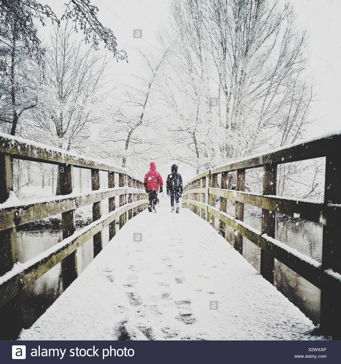 Rear view of two children walking across footbridge in the snow Stock Photo