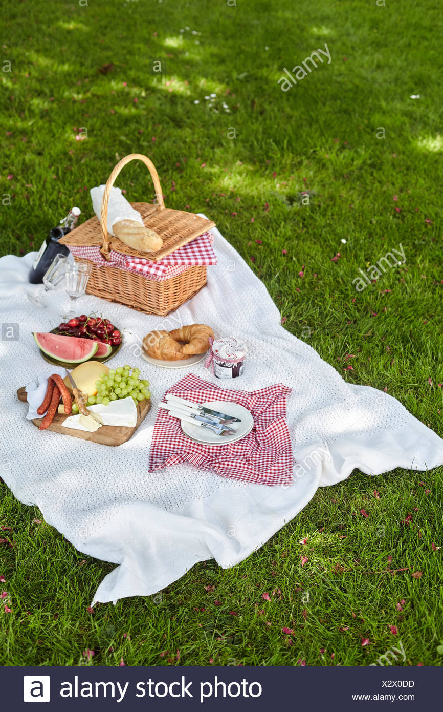 Wicker Picnic Hamper With Fresh Food And Wine Spread Out On