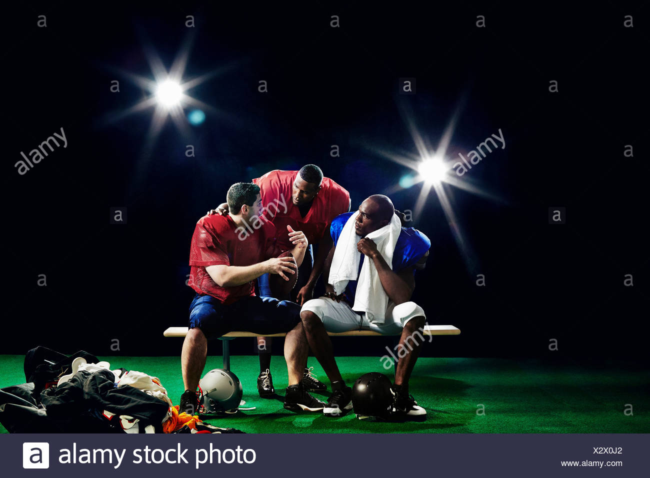 American footballers sitting on bench talking - Stock Image