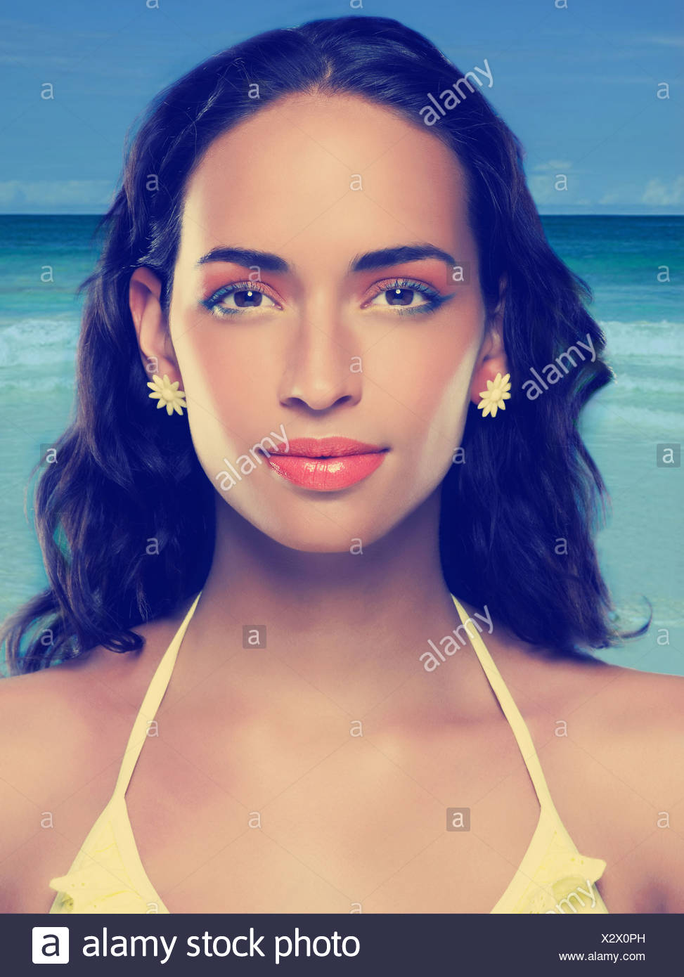 Young woman wearing yellow bikini and earrings Stock Photo