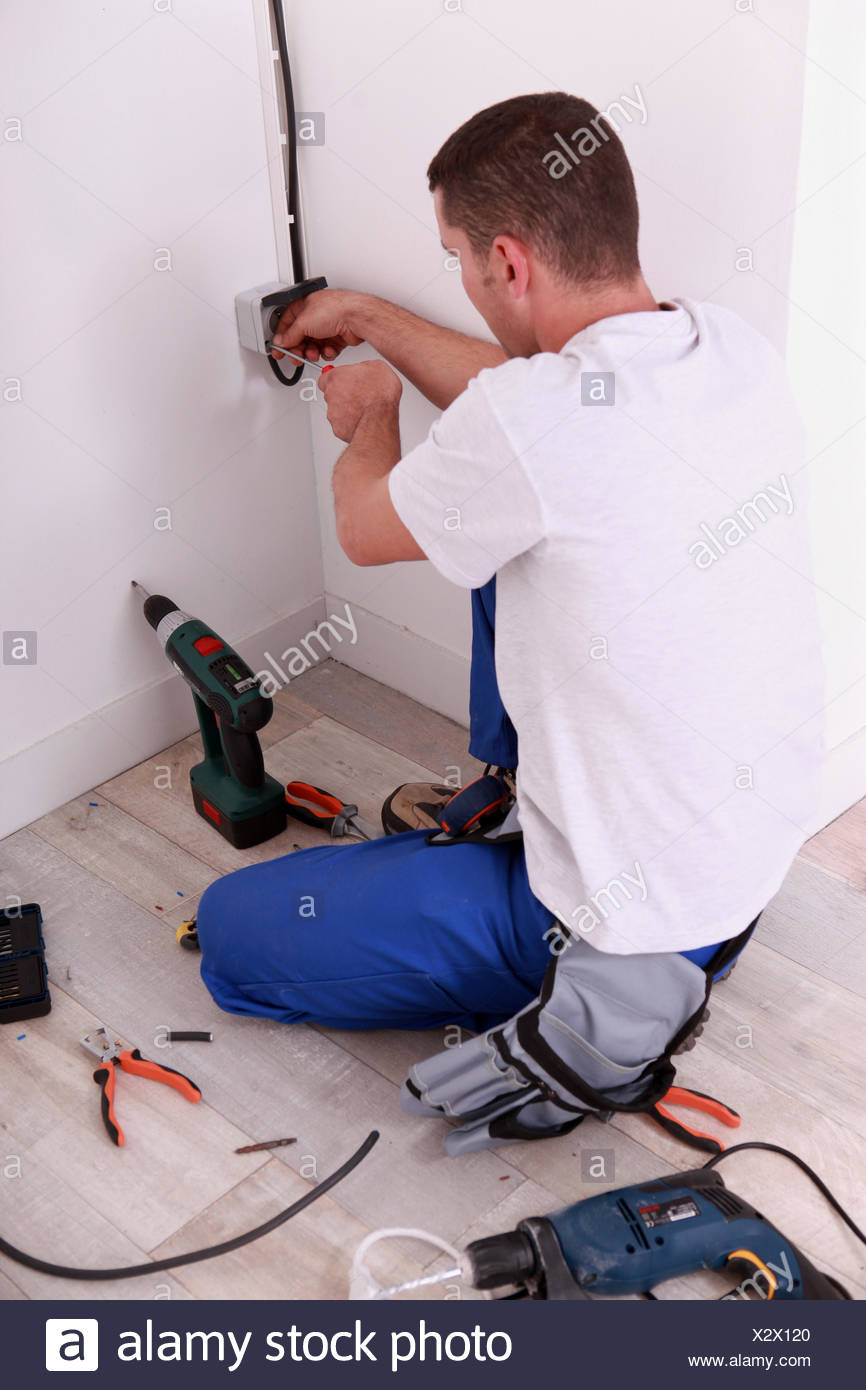 electrician screwing an electrical outlet - Stock Image