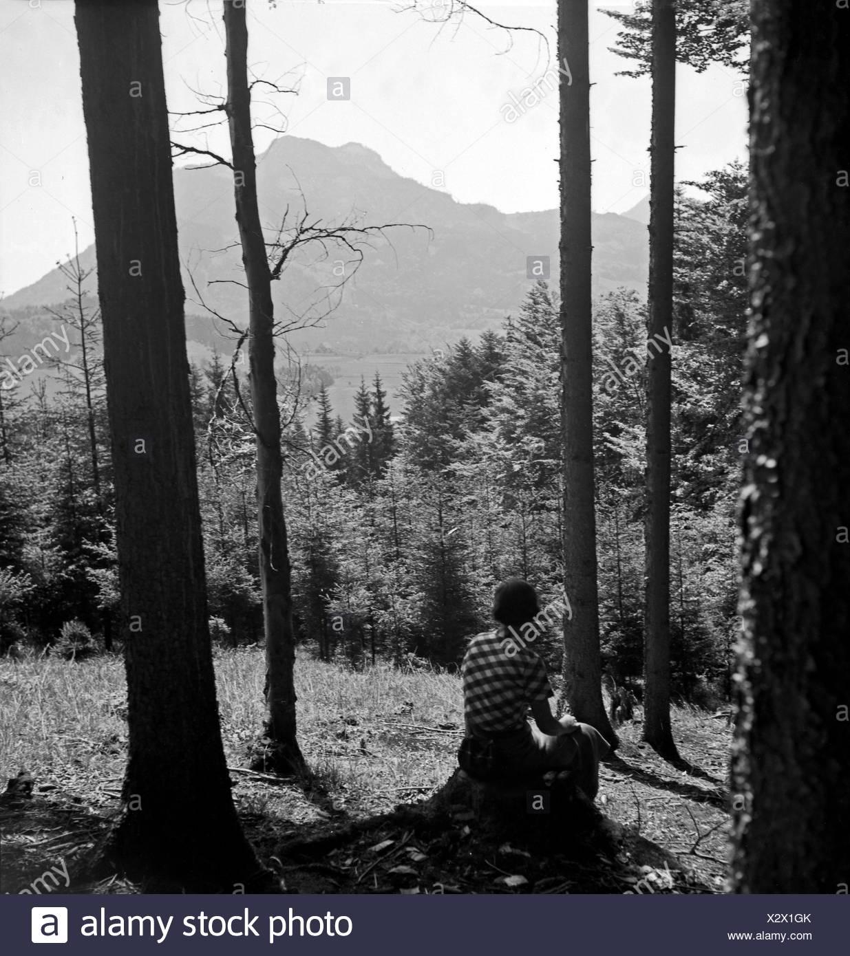 Eine Frau sitzt alleine im Wald, Deutschland 1930er Jahre. A woman sitting alone at a forest, Germany, 1930s. - Stock Image