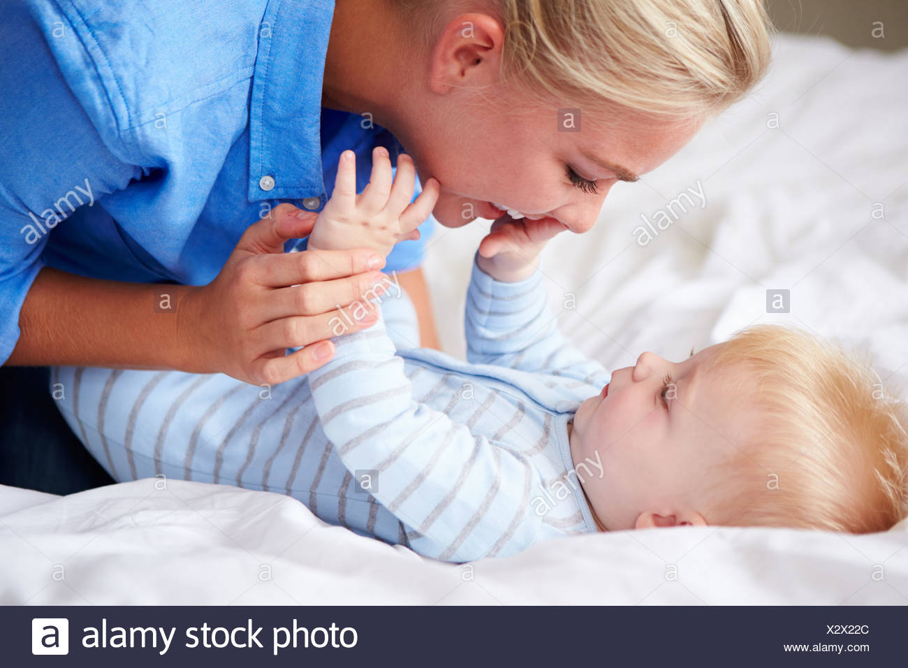 Mother Playing With Baby Son As They Lie In Bed Together - Stock Image