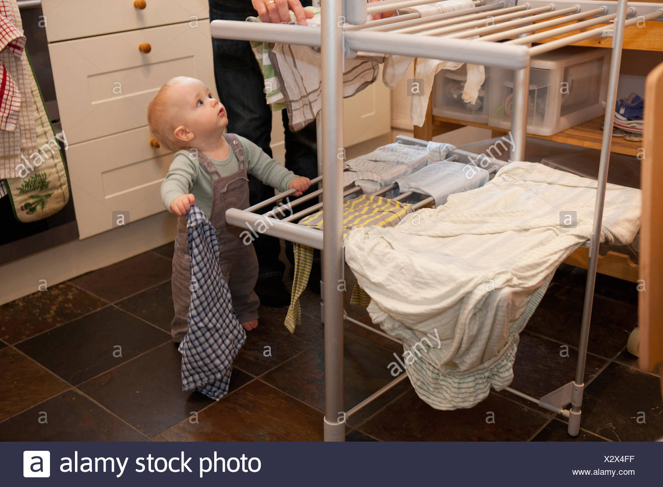 Baby boy and mother hanging laundry - Stock Image