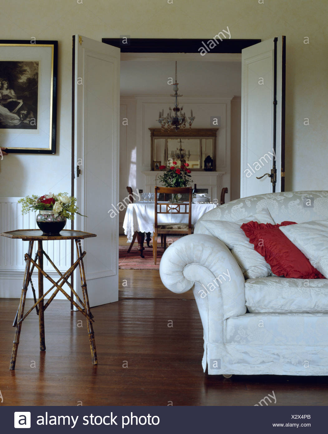 White Sofa And Small Bamboo Table In Living Room With Wooden Floor Double Doors Open To Dining