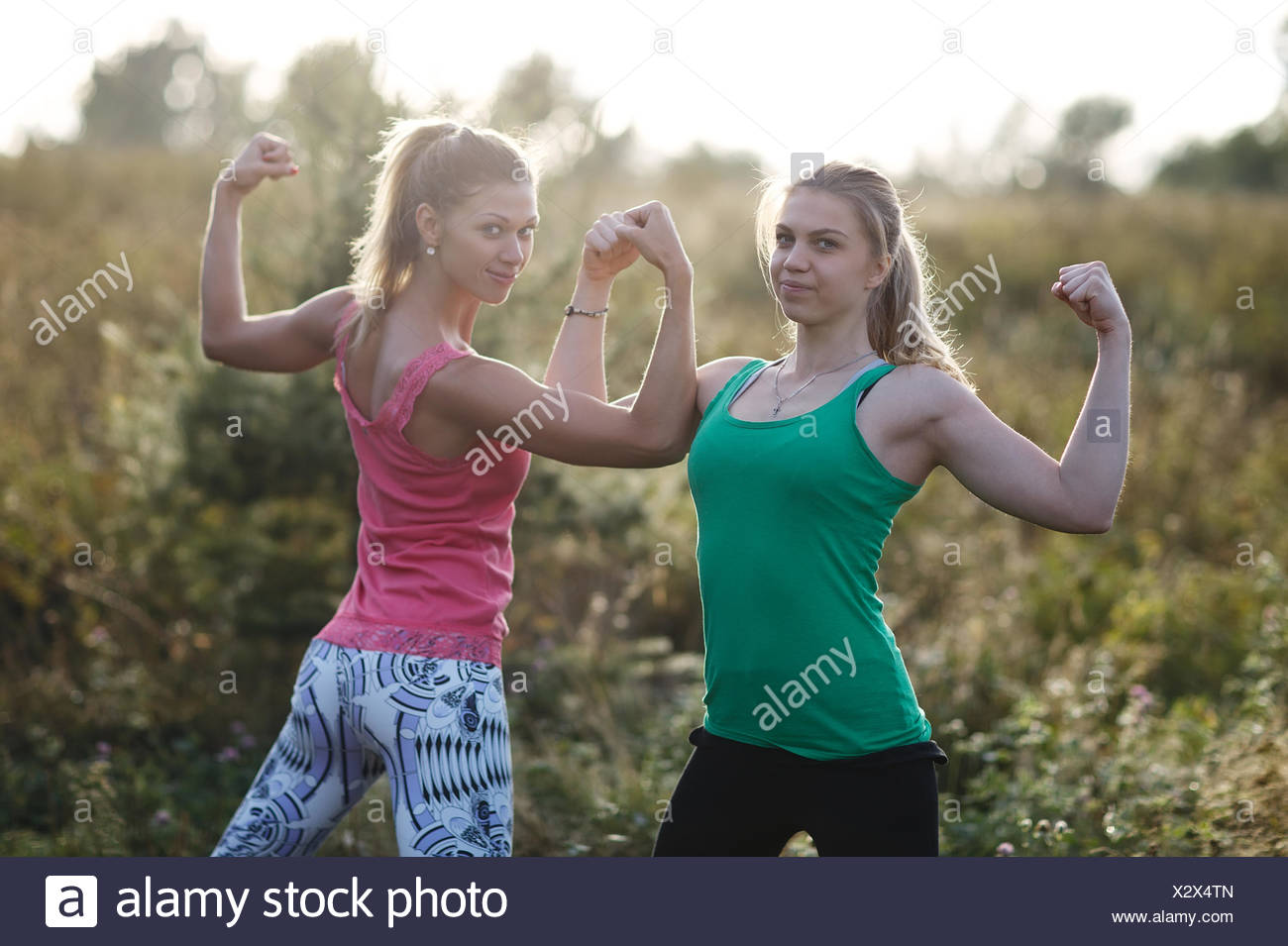 Two athletic girls flexing their arm muscles - Stock Image