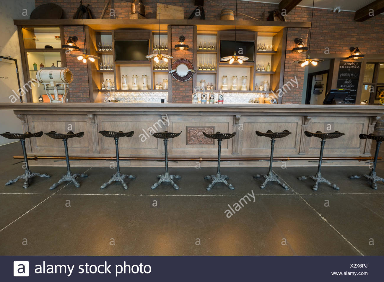 Stools lined along empty distillery bar - Stock Image
