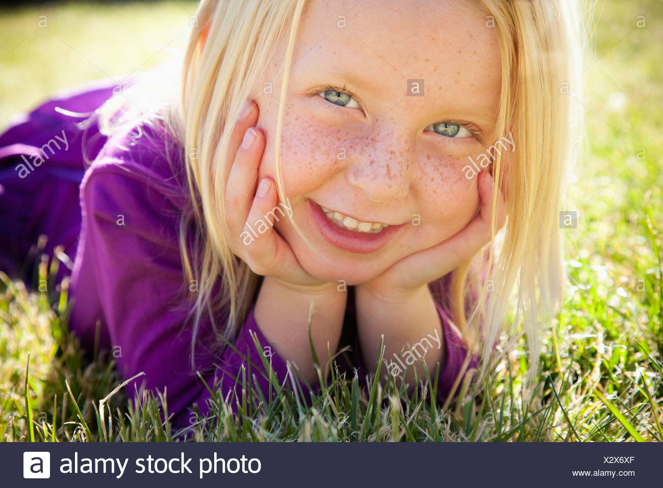 A young girl lying on the grass on her front with her chin resting on her hands. Laughing. Close up. Stock Photo