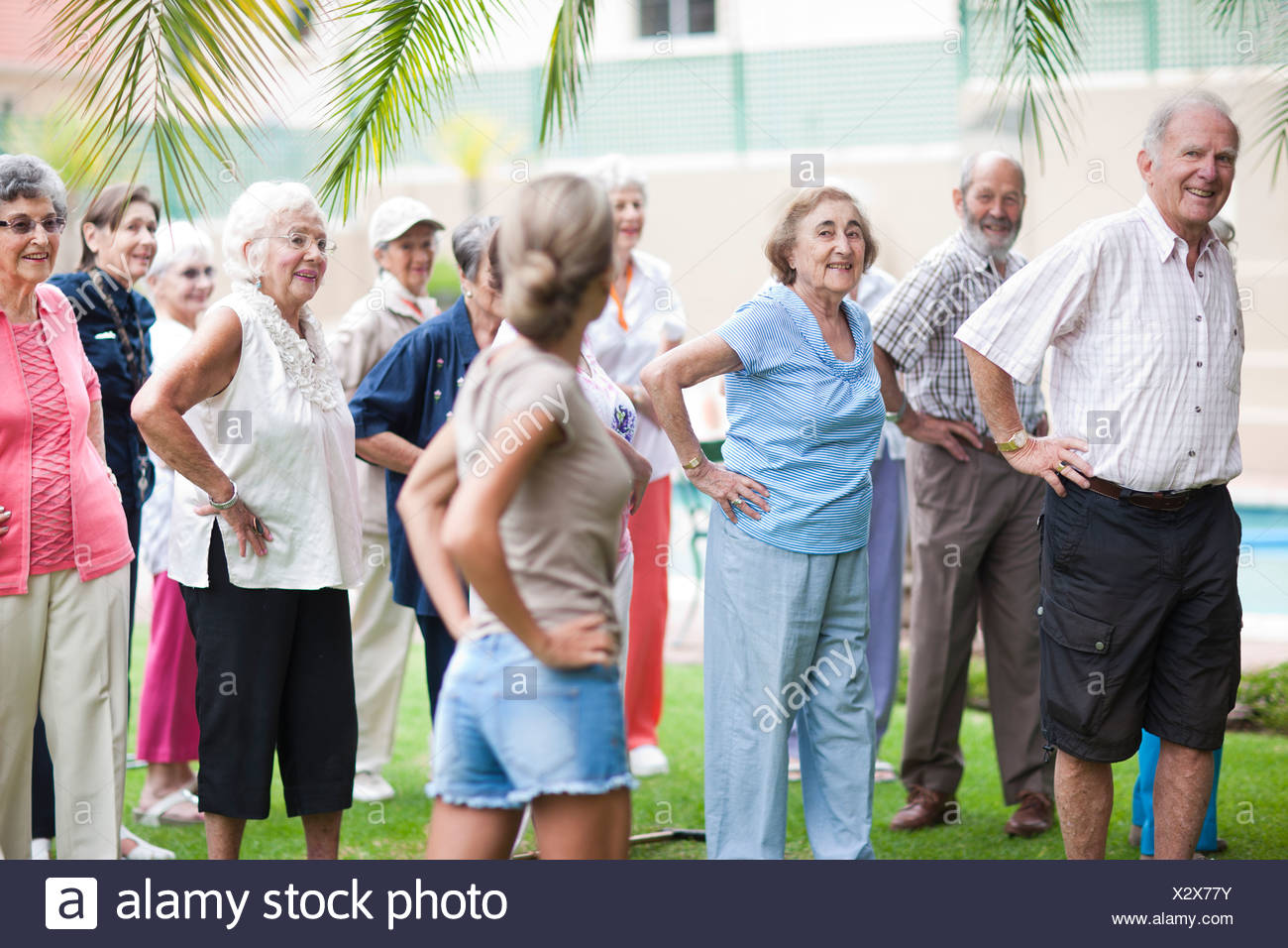 Large group of seniors exercising in retirement villa garden - Stock Image