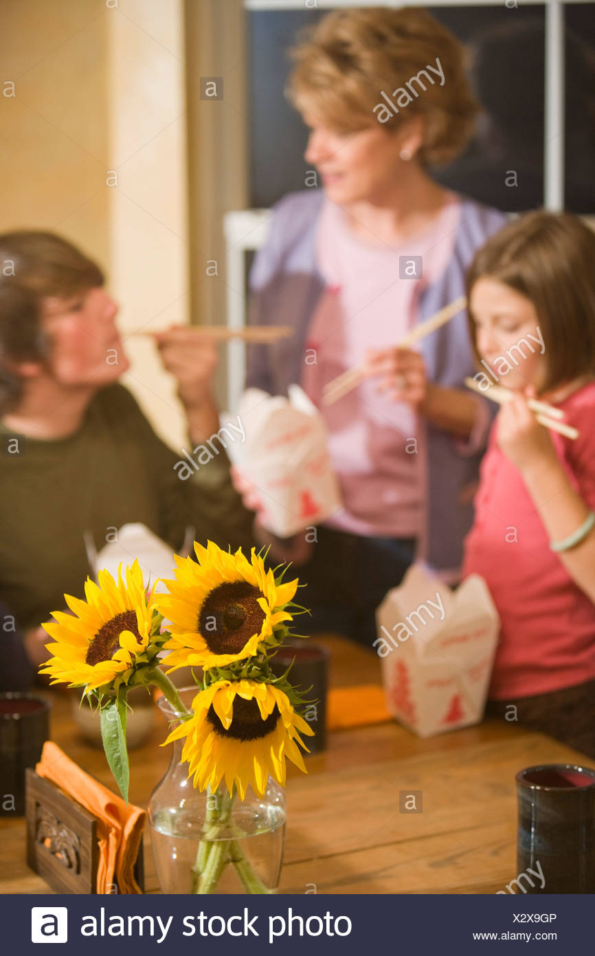 Family eating Chinese takeout for dinner at home, focus on flowers Stock Photo