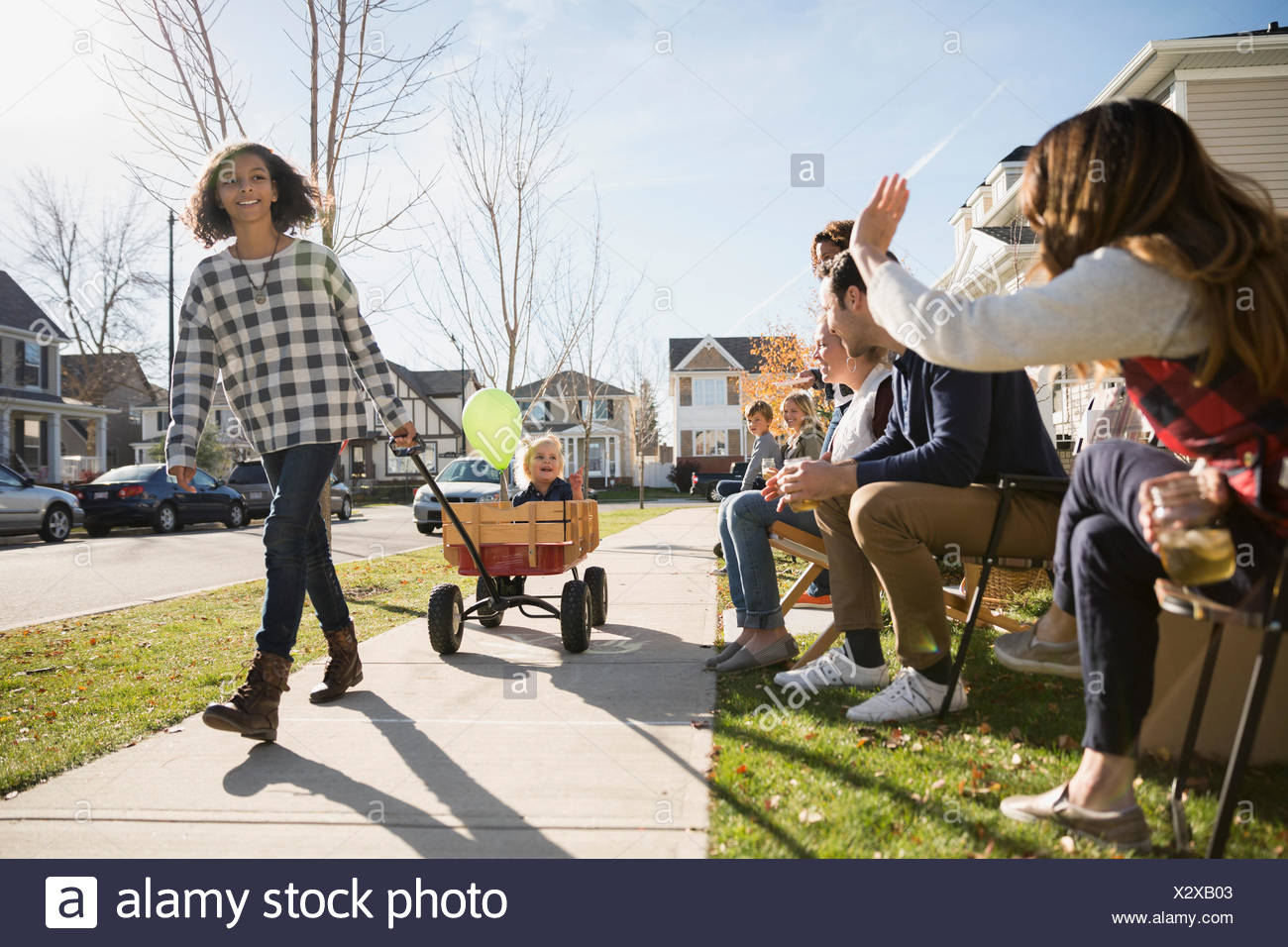 Neighbors waving at girl pulling friend in wagon - Stock Image