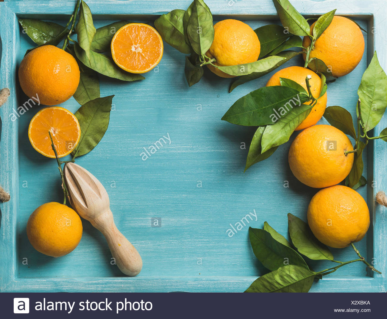 Fresh oranges with leaves on blue painted wooden background, top view, copy space, horizontal composition - Stock Image
