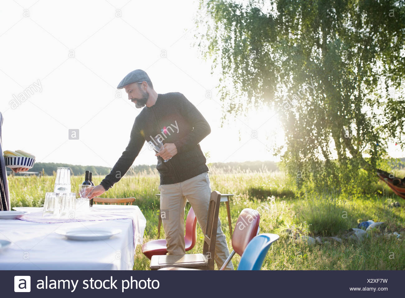 Man setting the table for garden party dinner in sunny summer rural yard - Stock Image
