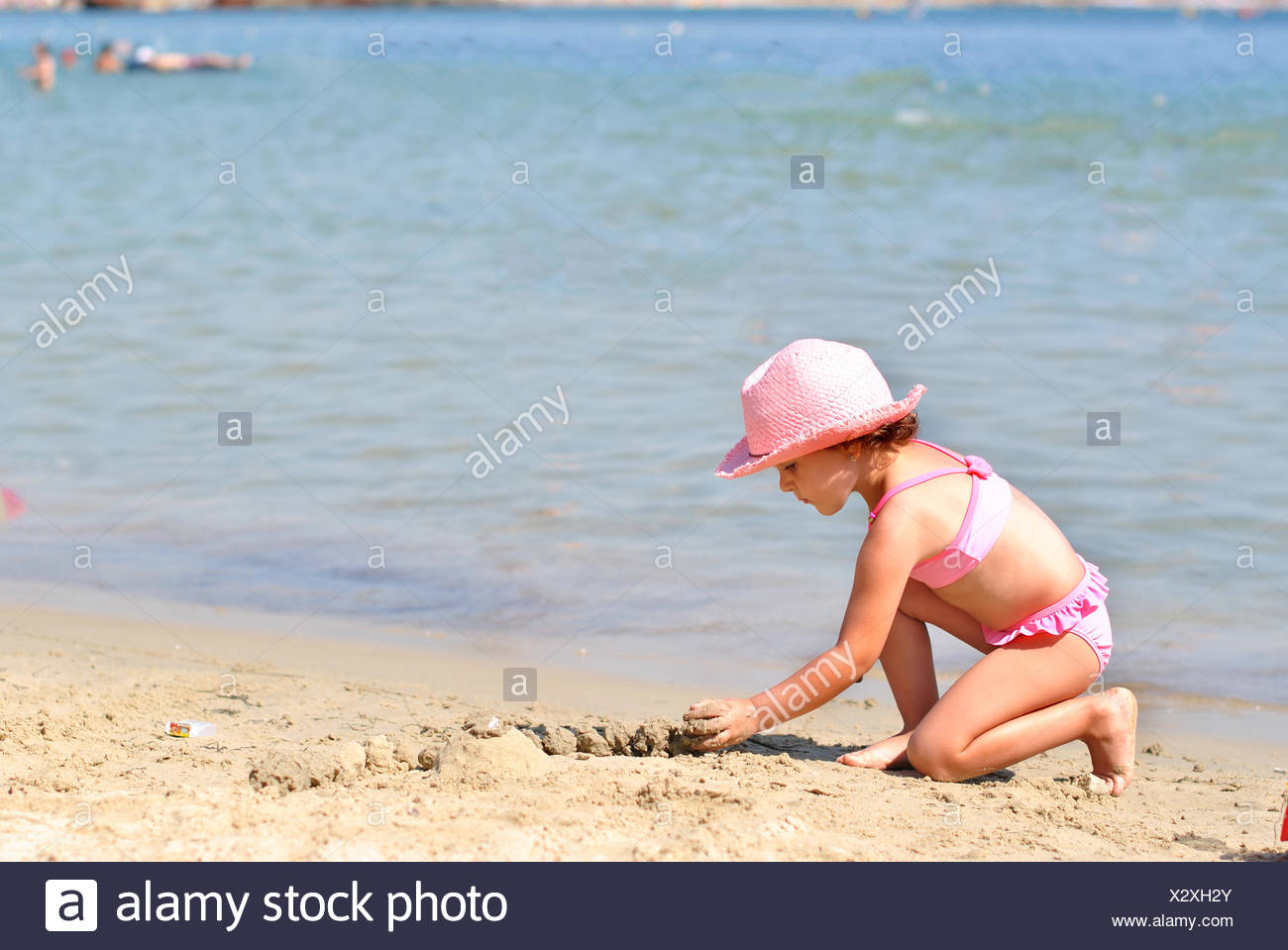 Girl (2-3 ) playing on sandy beach - Stock Image