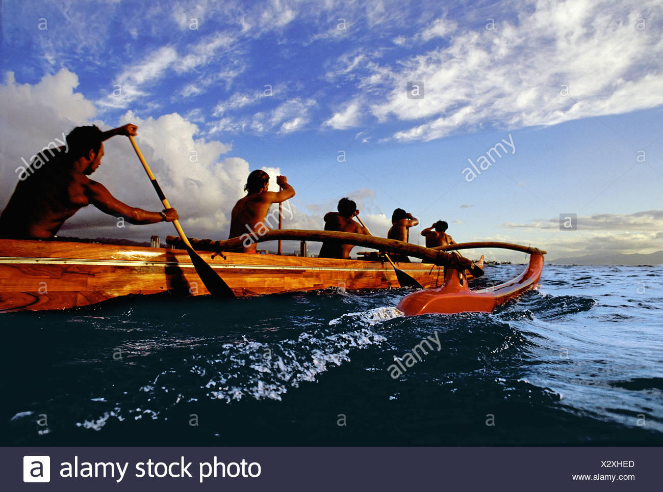 Paddlers in a koa canoe off Waikiki Beach on a beautiful afternoon, photographed from water level. Stock Photo