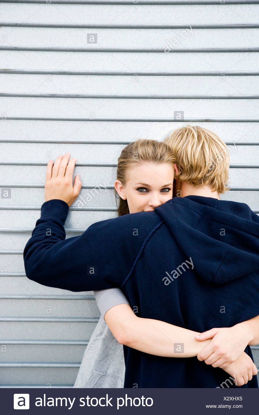Portrait of a young couple leaning against a metallic wall - Stock Image