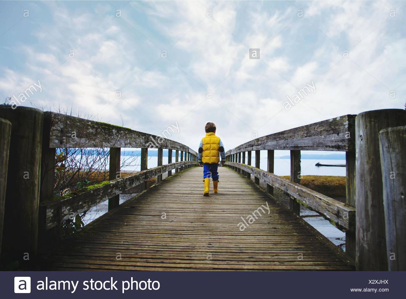 Boy (4-5) walking across wooden bridge - Stock Image