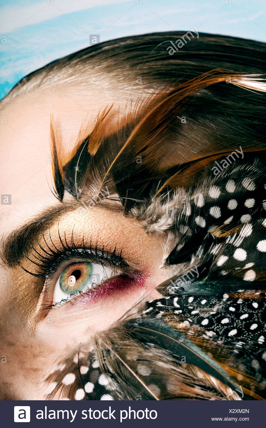 Young woman with Feathers around her eyes - Stock Image