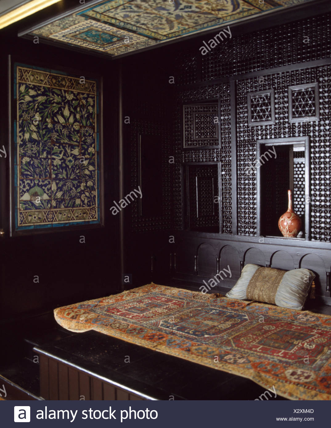 Old oriental rug on bed in Moroccan style bedroom Stock ...