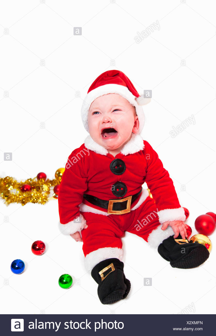 Cute baby in father Christmas outfit Stock Photo